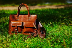 Retro brown shoes and man leather bag in bright colorful summer grass Stock Photos