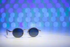 Retro brown sunglasses with blurry pink and turquoise background Royalty Free Stock Photo