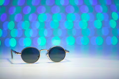 Retro brown sunglasses with blurry pink and turquoise background. Retro sunglasses with blurry pink and turquoise background Royalty Free Stock Photography