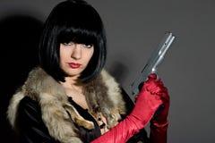 Retro brunette woman with gun Stock Image