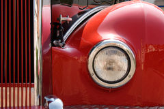 Retro Bus Headlight. Part of the cherry-red bus front with headlight and radiator grille. Close-up made made on the retro motor show in Germany stock image
