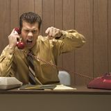 Retro business scene of angry man at desk. Caucasion mid-adult retro businessman sitting at desk talking on telephone with angry expression and gesture stock images