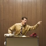 Retro business scene of angry man at desk. Royalty Free Stock Photo