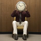 Retro businessman holding clock over face. stock photo