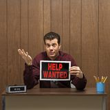 Retro businessman holding help wanted sign. Stock Images