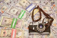 A retro camera on the background of money. Hobby and business in one photo royalty free stock photo
