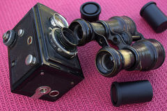 Retro camera and binoculars and photographic films. On the red background Stock Images