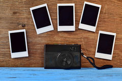 Retro camera and blank instant photos on a wooden surface Stock Image