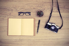 Retro camera with blank notebook on wooden table Stock Image