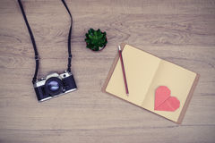 Retro camera with blank notebook on wooden table Royalty Free Stock Photo