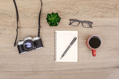 Retro camera with blank notebook on wooden table Royalty Free Stock Images