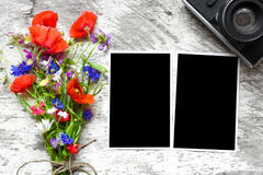 Retro camera and blank paper photo frames on wooden table with summer wildflowers Royalty Free Stock Photo