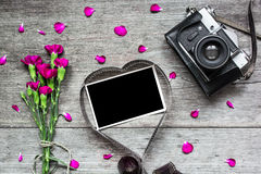 Retro camera and blank photo frame in heart shaped film with flowers Royalty Free Stock Photo