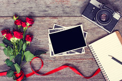 Retro camera and blank photo frame with red roses flowers Stock Photo