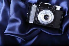 Retro camera on blue Royalty Free Stock Photos