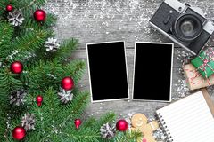 Retro camera and christmas blank photo frames with fir tree branches, decorations, gift boxes and lined notebook. Over rustic wooden background. mock up. flat Royalty Free Stock Photography