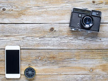 Retro camera, compass and smartphone. On a wooden planks stock image