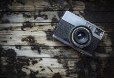Retro camera on a dark wooden background. Top view royalty free stock photos