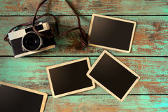 Retro camera and empty old instant paper photo album on wood table Stock Image