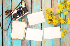 Retro camera and empty old instant paper photo album on wood table with flowers border design Royalty Free Stock Image