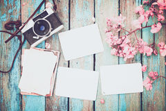Retro camera and empty old instant paper photo album on wood table with flowers border design Royalty Free Stock Photography