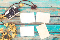 Retro camera and empty old instant paper photo album on wood table with flowers border design Stock Image