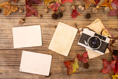Retro camera and empty old instant paper photo album on wood table with maple leaves in autumn. Border design - concept of remembrance and nostalgia in fall stock photography