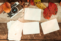 Retro camera and empty old instant paper photo album on wood table with maple leaves in autumn border design Royalty Free Stock Photo