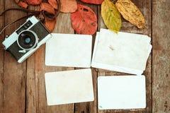 Retro camera en leeg oud onmiddellijk document fotoalbum op houten lijst met esdoornbladeren in het ontwerp van de de herfstgrens Royalty-vrije Stock Fotografie