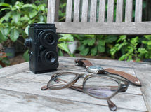 Retro camera, eyeglasses and watch on wooden background Stock Photography