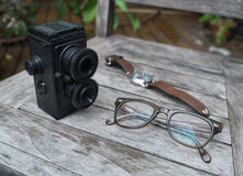Retro camera, eyeglasses and watch on wooden background Stock Photo