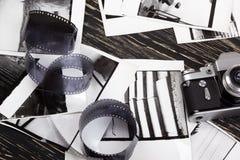 Retro camera, film and some old photos. Retro camera and some old photos on wooden table Royalty Free Stock Images