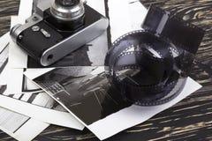 Retro camera, film and some old photos. Retro camera and some old photos on wooden table Royalty Free Stock Photo