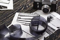 Retro camera, film and some old photos. Retro camera and some old photos on wooden table Royalty Free Stock Photography