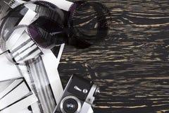 Retro camera, film and some old photos. Retro camera and some old photos on wooden table Stock Images