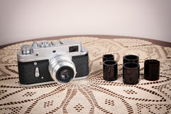 Retro camera and films. On the brown table with handmade tablecloth. Vintage style photo stock images
