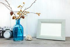 Retro camera, fotokader, vaas met droge bloemen op houten lusje stock fotografie