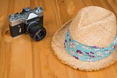 Retro camera and a hat on wooden background Stock Images