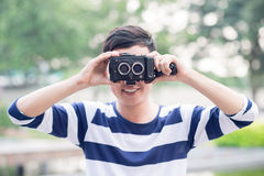 Retro camera. Image of a young man with a retro camera in hands Stock Photos