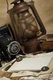 Retro camera, kerosene lamp and old photos. On the knitted cloth Stock Photos