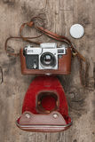 Retro camera in leather case on wooden background Stock Images