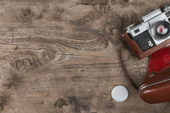 Retro camera in leather case on wooden background Stock Photo