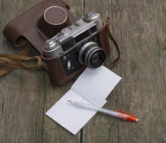 Retro the camera in a leather shabby cover and a notebook Stock Photos