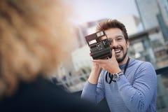 Retro camera. Man taking a photo with retro camera Stock Photos