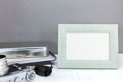 Retro camera, negative film roll and empty photo frame on grey b Stock Photos