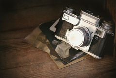 Retro camera with old photos on rustic wooden board, vintage background Stock Image