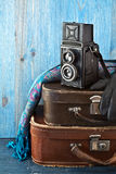 Retro camera and old suitcases. On a blue wooden background Stock Photos
