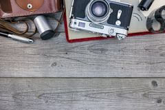 Retro camera, pen, negative films and photo album on wooden tabl. E flat view Royalty Free Stock Images