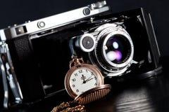 Retro camera and pocket watch. Old retro camera and pocket watch on black background. Vintage camera closeup Royalty Free Stock Photo