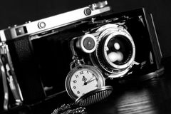 Retro camera and pocket watch. Old retro camera and pocket watch on black background. Vintage camera closeup Royalty Free Stock Photos